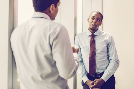 Serious businessman disusing problem with coworker in office. African-American entrepreneur standing at office window and talking to employee. Meeting of coworkers concept Imagens