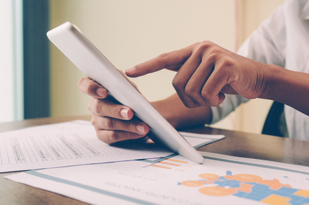 Closeup of person holding and using tablet. Papers lying on desk. Marketing research concept. Cropped view. Archivio Fotografico - 115382688