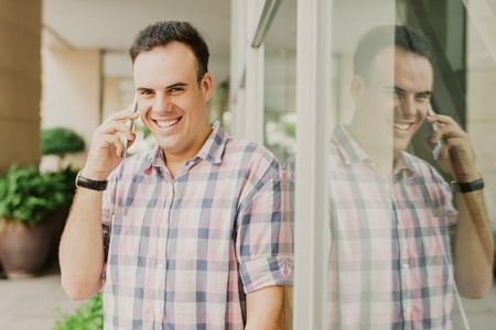 Cheerful optimistic young man calling on mobile phone and looking at camera. Jolly excited brunette guy leaning on glassy wall and chatting on phone. Freelance manager concept Imagens - 115382721