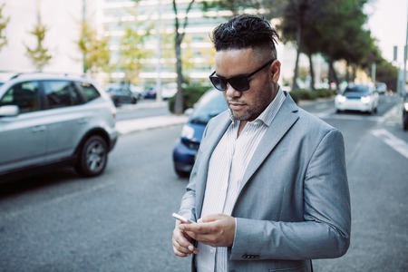 Portrait of confident businessman in sunglasses with smartphone. Young Latin American businessman standing on road side phoning for taxi. Mobile communication concept