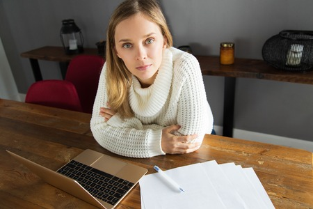 Content attractive young woman in white sweater working at home. Serious lady sitting at table and using laptop. Freelancer concept 版權商用圖片