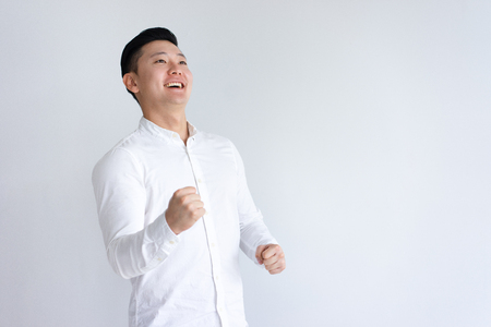 Cheerful Asian man pumping fists and looking away. Guy celebrating achievement. Success concept. Isolated front view on white background.