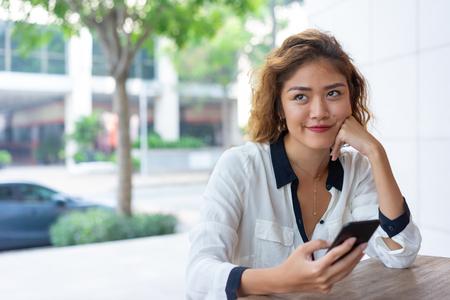 Chica de oficina asiática positiva descansando en la cafetería de la calle. Hermosa mujer joven con smartphone al aire libre durante el almuerzo. Concepto de conexión inalámbrica