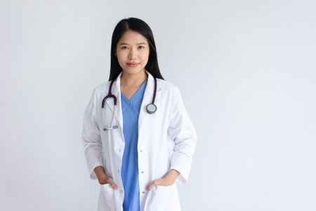 Content young female doctor posing at camera. Pretty woman wearing white coat and standing. Medicine and healthcare concept. Isolated front view on white background. 免版税图像