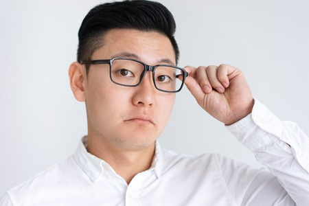 Confused Asian man adjusting glasses. Attractive young guy looking at camera. Confusion concept. Isolated front view on white background.