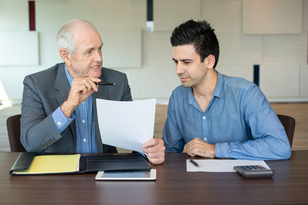 Business partners discussing contract. Serious senior entrepreneur explaining work to his young coworker. Business meeting concept