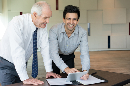 Cheerful entrepreneur showing application to colleague. Smiling businessmen discussing information on tablet computer at meeting. Successful work concept Reklamní fotografie