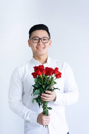 Smiling Asian man holding bunch of roses. Young man looking at camera. Flowers and gift concept. Isolated front view on white background.