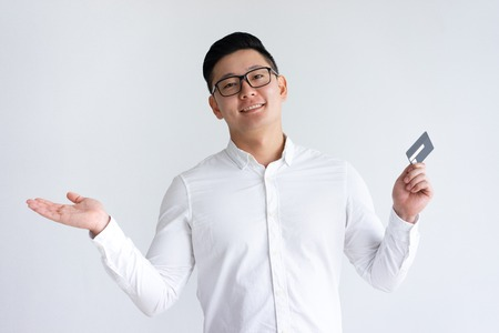Smiling Asian man holding credit card and throwing up hand. Handsome young guy looking at camera. Cashless payment concept. Isolated front view on white background. Stockfoto