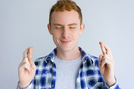 Smiling handsome man showing crossed fingers gesture. Guy making wish with his eyes closed. Wish concept. Isolated front view on white background.