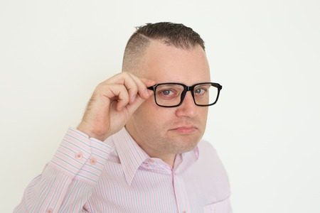 Serious suspicious office employee touching temple of eyeglasses. Closeup of young Caucasian man adjusting glasses and looking at camera. Glasses wearing concept Stok Fotoğraf