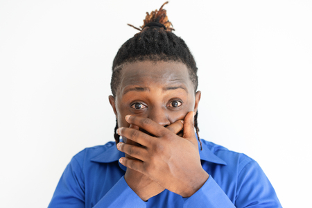 Shocked black man covering mouth with both hands. Young guy looking at camera. Shock concept. Isolated front view on white background.