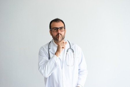 Serious handsome male doctor showing silence gesture. Middle-aged guy wearing white coat. Medical secrecy concept. Isolated front view on white background.