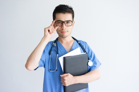 Serious young male doctor holding folder and documents. Handsome guy standing, adjusting glasses and wearing blue medical uniform. Professional doctor concept. Isolated front view on white background.