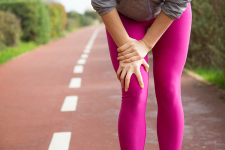 Female jogger wearing pink tights, injuring knee. Closeup of female hand holding leg. Athletic injury concept Stockfoto