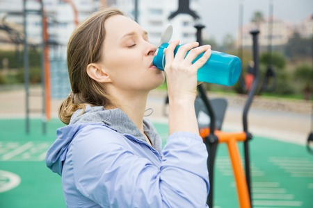 Tired fit girl feeling thirsty during physical exercises. Young woman in sports hoodie drinking water from blue flask or shaker. Fitness or thirst concept