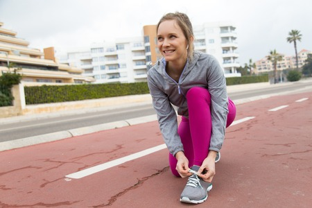 Positive woman in leggings standing on one knee and tying lace outdoors. Determined young lady training on stadium track. Sport concept