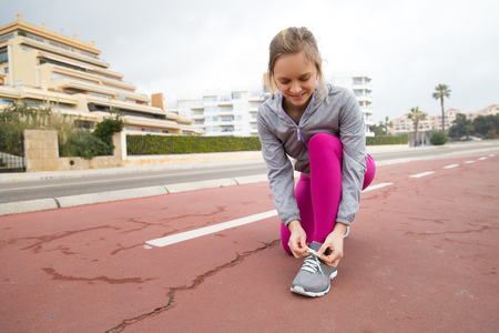 Smiling runner tying lace of sport shoe on stadium. Content pretty young woman in sports clothing standing on one knee while adjusting shoelace. Jogger concept Stock Photo