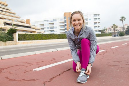 Happy young jogger taking break to tie shoelace. Cheerful woman in pink leggings adjusting lace of sport shoe. Runner concept