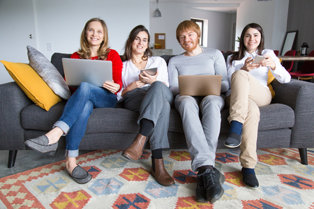 Group of freelance colleagues working at home. Four young people sitting on couch together and using gadgets. Freelance or home office concept