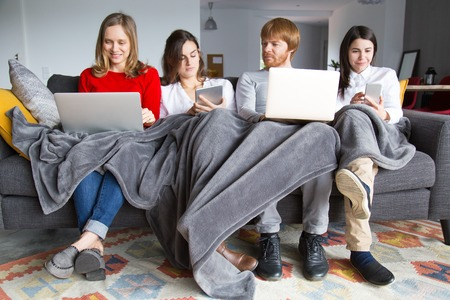 Group of students working on their home assignment. Four young people sitting on couch together covered with plaid and using gadgets. Student community concept Stock Photo