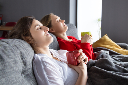 Female roommates having cold and resting at home. Peaceful women sitting on couch with closed eyes and holding mugs. Flu concept