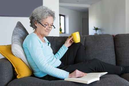 Smiling positive retired lady excited with interesting novel. Grey haired senior woman in casual and eyeglasses resting on couch and reading book over cup of tea. Reading books concept