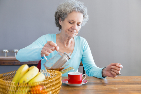 Serious senior lady keeping healthy diet. Elderly woman sitting at table with fruit and pouring tea. Healthy diet concept