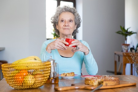Pensive retired lady enjoying coffee break at home. Senior grey haired woman drinking tea and eating pie. Retirement concept