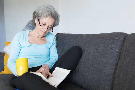 Serious senior lady studying notes over cup of tea. Mature grey haired woman sitting on couch, holding yellow cup and reading book. Reading concept