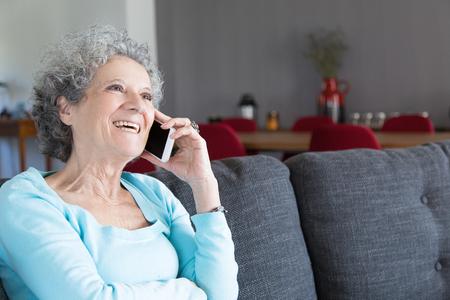 Porträt der glücklichen älteren Frau, die am Telefon spricht und lacht. Oma sitzt auf der Couch und benutzt Smartphone. Kommunikations- und Altersvorsorgekonzept