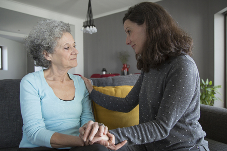 Woman holding senior mother hands and comforting her. Mother and daughter talking and sitting on sofa with home interior in background. Caring for aging parents concept.