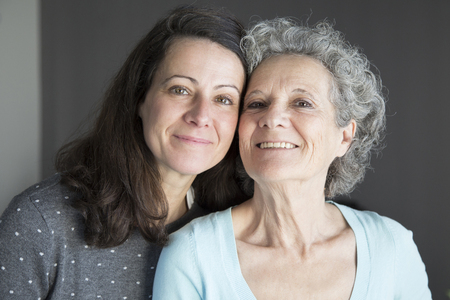 Relaxed senior woman and her daughter posing at camera. Mother and daughter with grey wall in background. Family portrait concept. Front view.
