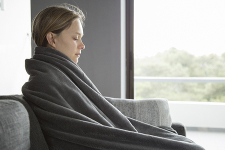Sick young fair-haired Caucasian woman in purple sweater covered with grey blanket sitting on grey sofa in living room, keeping her eyes closed, meditating. Illness, lifestyle concept Stock fotó