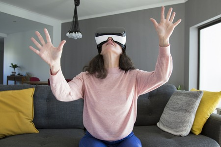 Surprised woman in virtual reality goggles gesturing hands while playing game. Curious woman sitting on sofa in living room. Video game concept 版權商用圖片