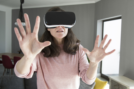 Young woman in virtual reality goggles playing online game. Concentrated woman pushing hands forward while walking over room. Technology concept