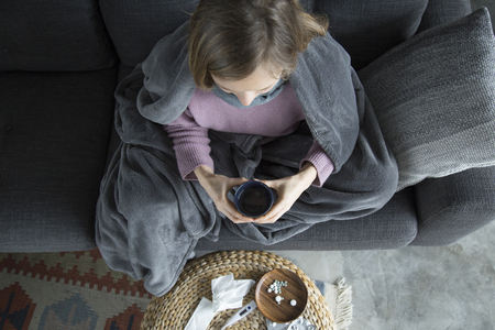 Top view of sick young fair-haired woman in purple sweater covered with grey blanket sitting on grey sofa in living room, holding green cup in hands. Illness, pain concept Banco de Imagens - 121990618