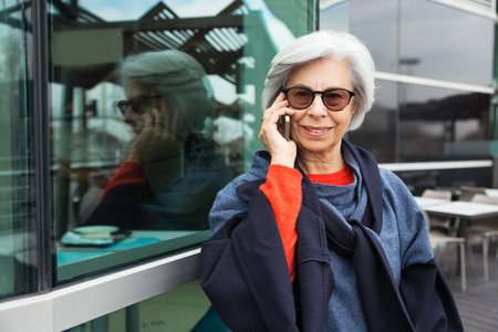 Happy cheerful senior lady speaking on cell and smiling at camera. Grey haired mature woman in sunglasses and overcoat enjoying phone talk. Good news concept Banque d'images - 118376752