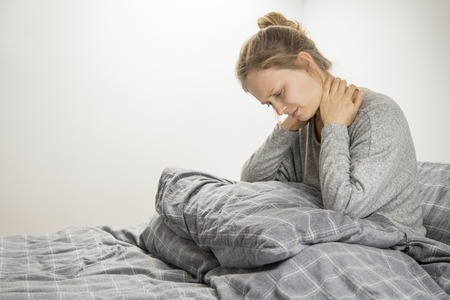Frustrated girl feeling neck ache after waking up. Young woman suffering from osteochondrosis. Healthcare concept