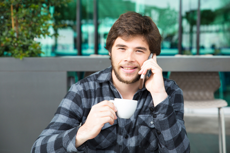 Happy positive young man learning good news from phone talk. Smiling guy in casual enjoying morning coffee and speaking on cellphone. Good news and coffee concept Banque d'images - 118576289