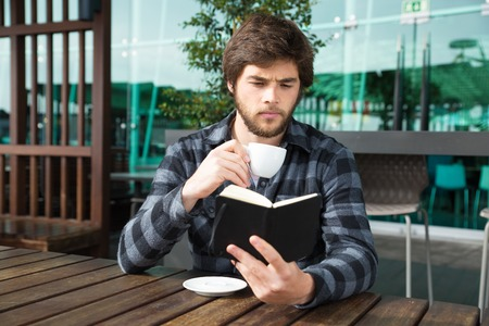 Serious guy excited with interesting book story. Focused young man in casual reading book over morning cup of coffee in street cafe. Reading book concept Imagens - 118576461