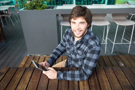 Positive happy guy enjoying free Wi Fi in outdoor cafe. Joyful young man in casual using tablet in street coffee shop and smiling at camera. Free Wi Fi zone concept