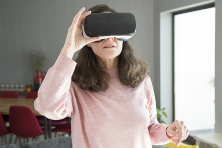 Curious young woman in VR headset walking over living room. Content lady playing videogame. Virtual reality concept Imagens