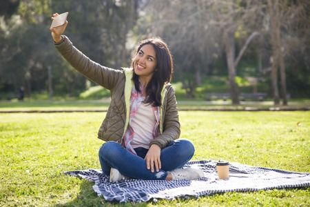 Cheerful hipster girl excited with self portraits. Young woman in casual jacket sitting on grass in park and taking selfie on her smartphone. Photo concept Imagens