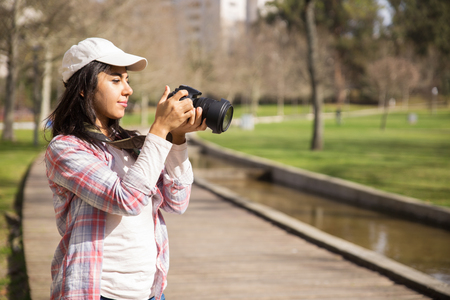 Pensive traveler walking around park and taking pictures of landmarks. Young woman wearing casual shirt and cap checking pictures on camera screen. Hobby concept