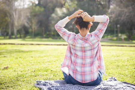 Student girl in checked shirt and jeans enjoying leisure in park. Back view of young woman sitting on grass, tiding up hair or making bun. Leisure outdoors concept