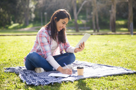 Positive student girl working on home assignment outdoors. Young woman in casual sitting on grass in park, using tablet and taking notes. Studying in university concept