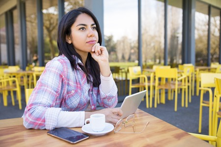 Pensive woman using gadgets and drinking coffee in cafe. Pretty young lady wearing casual shirt and sitting at table with chairs and building in background. Leisure and technology concept. Imagens