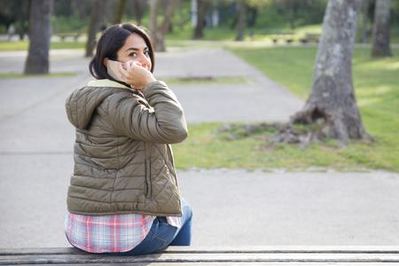 Vista trasera de la chica estudiante hablando por teléfono en el parque. Mujer joven en chaqueta casual sentado en un banco, hablando por celular y girando la cabeza. Concepto de conversación telefónica