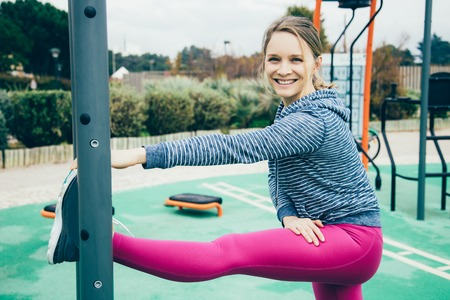 Smiling young woman stretching leg on sports ground. Pretty lady wearing sportswear, looking at camera and leaning on sports equipment. Outdoor workout concept. Side view.